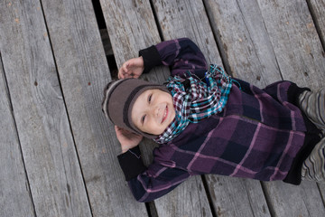 Two year old little boy laughs and lies on a grey wooden background