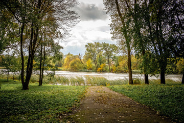 The road in the park leading to the river in the autumn. Autumn landscape with river and trees_