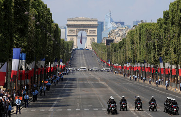 French police and gendarmes survey the Champs-Elysees Avenue after the traditional Bastille Day military parade as part of tight security measures in Paris