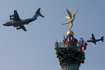 "An Airbus A400M aircraft and a C160 Transall from the French Air Force flies past the ""Genie de la Liberte"" gilded figure (Spirit of Freedom) on top of the Place de la Bastille's July Column in Paris"