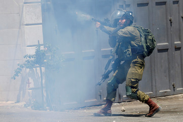 An Israeli soldier fires at Palestinians during clashes near Hebron in the occupied West Bank