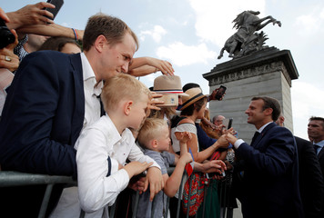French President Emmanuel Macron shakes hands with people after the traditional Bastille Day military parade on the Champs-Elysees in Paris