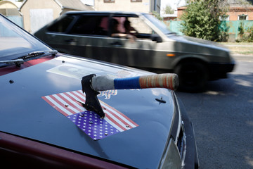 An axe is knocked into the motor hood of an old Lada car, with a sticker depicting a U.S. flag seen on it, in Krasnodar
