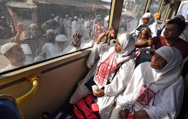 Muslim pilgrims wave towards their relatives before leaving for the annual haj pilgrimage to the holy city of Mecca, in Guwahati