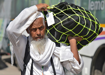 A Muslim pilgrim carries his belongings as he leaves for the annual haj pilgrimage to the holy city of Mecca, in Guwahati