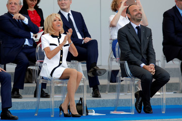 Brigitte Macron, the wife of French President Emmanuel Macron and Prime Minister Edouard Philippe attend the traditional Bastille Day military parade on the Champs-Elysees Avenue in Paris