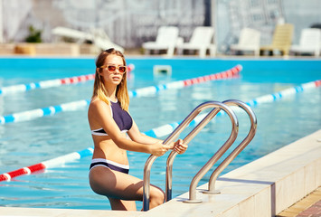 Pretty girl in sunglasses coming out from the water of a swimming pool
