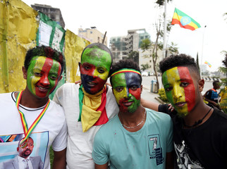 Residents, with painted Ethiopian national flag on their faces, attend a ceremony to welcome Eritrea's President Isaias Afwerki for a three-day visit, at the Bole international airport in Addis Ababa