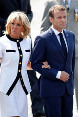 French President Emmanuel Macron and his wife Brigitte Macron leave after the traditional Bastille Day military parade on the Champs-Elysees in Paris