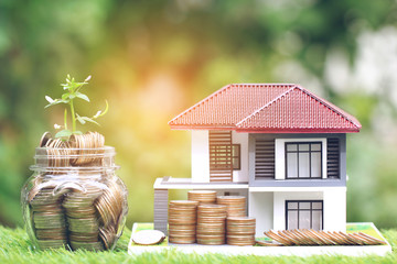 Plant growing on coins money in glass bottle with model house on natural green background,Interest rates and Banking concept