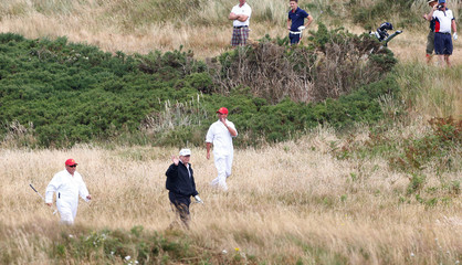U.S. President Donald Trump waves as walks at his golf resort, in Turnberry