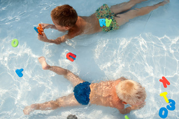 Two happy children play in swimming pool with plastic letters and numbers for bathroom. Brothers are happy together in warm water on sunny summer day. Concept of teaching games for preschoolers.