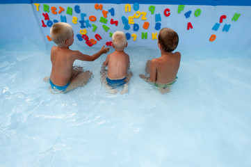 Three happy children play in swimming pool with plastic letters and numbers for bathroom. Brothers are happy together in warm water on sunny summer day. Concept of teaching games for preschoolers.