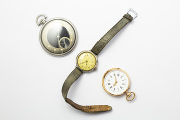 Set of watches on white background with a classic gold pocket watch a black and silver pocket watch and a wristwatch with worn leather straps