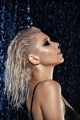 Glamor beauty portrait of a blonde girl with wet hair and skin.