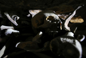 A skull and bones are seen inside a recently discovered burial shaft near Egypt's Saqqara necropolis, in Giza