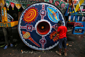 """A Hindu boy prays as he touches a """"Rath"""", or the chariot of Lord Jagannath, during the annual Rath Yatra, or chariot procession, in Kolkata"""