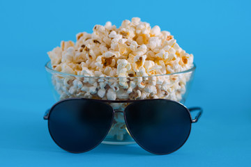 Popcorn and glasses on a blue background. Cinema background.