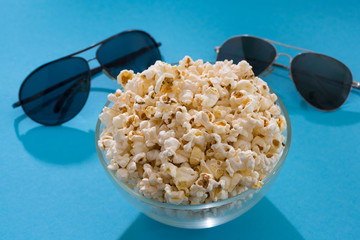Popcorn and glasses on a blue background. Cinema background. Concept pastime, entertainment and cinema.