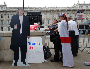Demonstrators stand next to a cardboard cut-out of U.S. President Donald Trump in London
