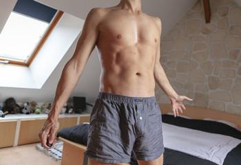 jeune homme torse-nu qui se réveille le matin en bombant le torse
