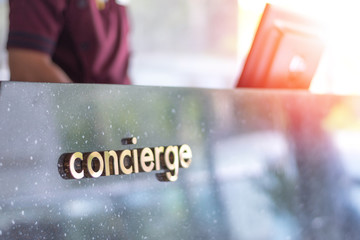 Concierge service desk counter with staff team working in front of hotel with tourist business customer.