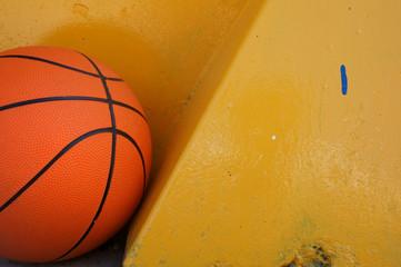 Orange basketball lying under yellow wall