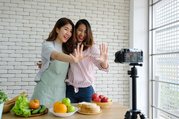 Two young asian woman food bloggers talking while recording video, vlog concept, people and technology communication