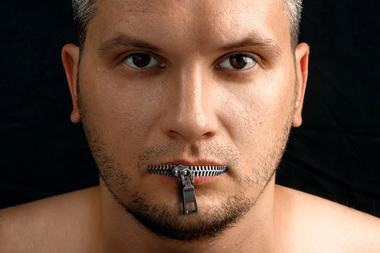 A man's mouth is closed with a zipper from his clothes. Photoshop. Black background. The concept of freedom of speech, closed mouth, silence problems, withholding information, pressing the media.