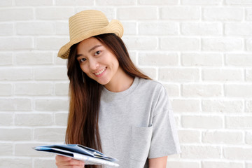 Young asian woman traveler holding map and smiling in white room with copy space, people summer holiday vacation background concept