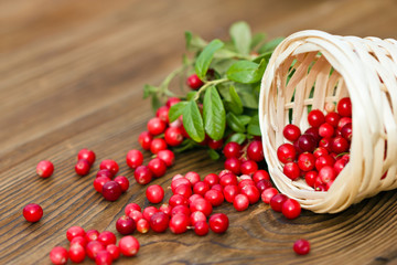 cranberry berries in a wicker basket on a wooden background.