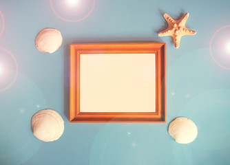 Summer beach holiday concept. Photo frame and seashell decoration on blue background