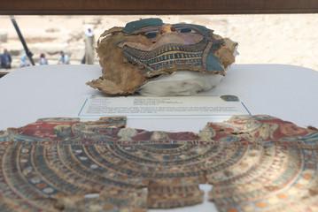 A broken mummy mask is seen inside a glass casing, on display near Egypt's Saqqara necropolis,in Giza