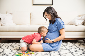 Son Kissing Abdomen Of Pregnant Mom In Living Room