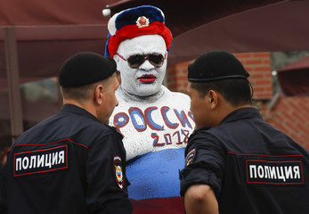 Policemen stalk to a man with a Russian traditional Ushanka hat and a body-painting, depicting the colours of the Russian flag, in Moscow