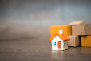 Miniature house with paper box background using as property, e-commerce and business concept