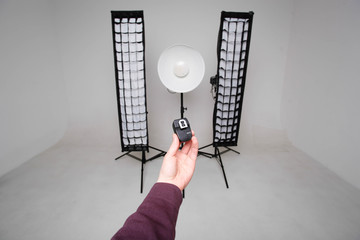 The hand holds the synchronizer for photographic equipment