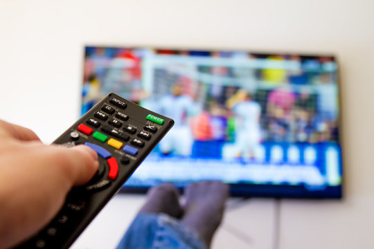 Close-up macro of man's hand with TV remote control watching a soccer match