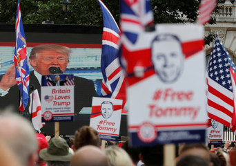 Demonstrators hold placards supporting EDL founder Tommy Robinson and U.S. President Donald Trump in London