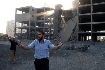 Palestinian policeman loyal to Hamas reacts in front of a building that was hit in an Israeli air strike in Gaza City