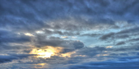 Cloudy, blue, rainy sky with clouds and sun. Colorful evening nature.