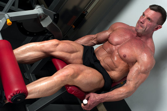 Mature high level bodybuilder with relief strong body. Muscular middle aged fitness model exercising on legs simulator in the gym