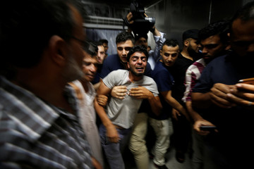 The brother of a Palestinian teenager who was killed in an Israeli air strike, reacts in Gaza City