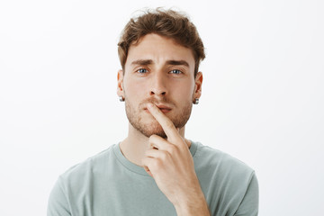 Portrait of smart focused attractive guy in earrings with short curly hair, holding index finger on lip and gazing with thoughtful expression at camera, thinking or making decision