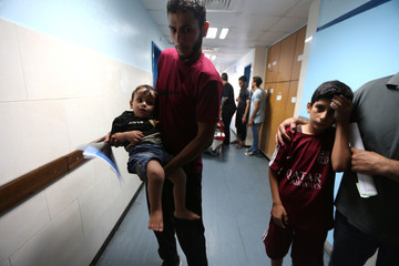 Palestinian boys are brought into the hospital following Israeli air strikes in Gaza City