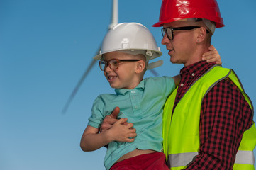 Engineer in the second generation. Portrait of a little positive boy in the hands of his father's engineer's in glasses and helmets against the background of windmill and blue sky