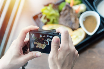 Woman taking food photo on camera at restaurant with rustic wood table.