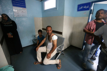 Wounded Palestinian sits at the hospital following Israeli air strikes in Gaza City