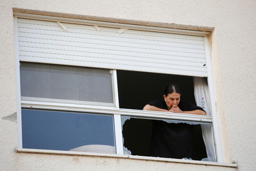 An Israeli woman looks out of a broken window at the southern city of Sderot, on the Israeli side of the Israel - Gaza border