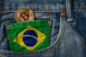 Golden BITCOIN (BTC) cryptocurrency in the pocket of jeans with the flag of Brazil